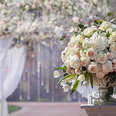 Beautiful bouquet of roses in a vase on a background of a wedding arch. Beautiful set up for the wedding ceremony.